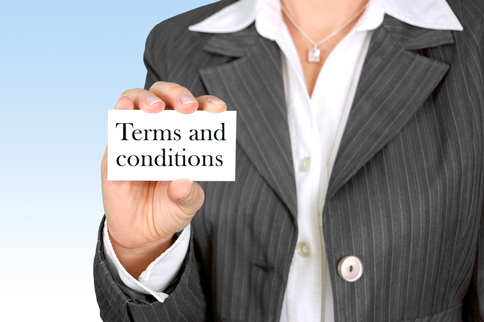 A professional holding a terms and conditions card